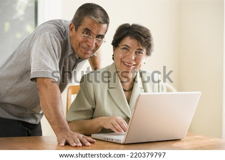 Portrait of mature couple with laptop - stock photo