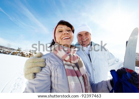Portrait of mature couple with skis outside - stock photo