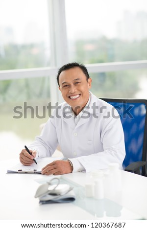 Portrait of mature doctor sitting in his office - stock photo