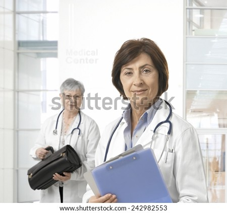 Portrait of mature female doctor, standing at hall of medical center. - stock photo
