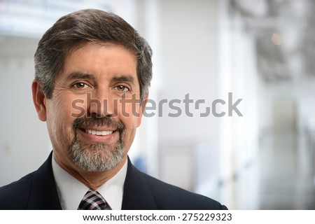 Portrait of mature Hispanic businessman smiling inside office building - stock photo