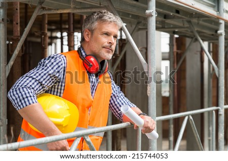 Portrait Of Mature Male Architect With Hardhat And Blueprint Thinking About Project - stock photo