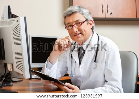Portrait of mature male doctor with clipboard sitting in front of computer at clinic - stock photo