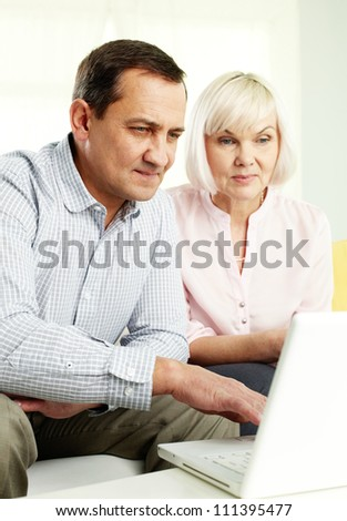 Portrait of mature man and his wife working with laptop at home - stock photo