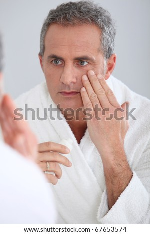 Portrait of mature man applying moisturizer on his face - stock photo