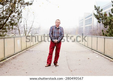 Portrait of mature man in glasses and plaid shirt standing on misty walkway leaning on his wooden cane - stock photo