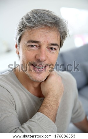 Portrait of mature man relaxing at home in sofa - stock photo