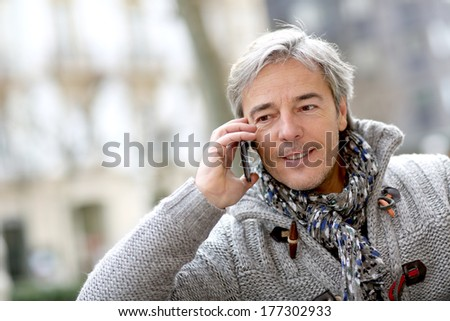 Portrait of mature man talking on phone in street - stock photo