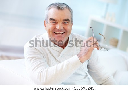 Portrait of mature man with eyeglasses in hand looking at camera - stock photo
