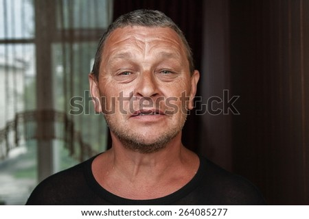 Portrait of mature man with lined face and dark suntan. - stock photo