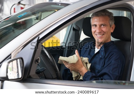 Portrait Of Mature Mechanic Sitting In Car At Workshop - stock photo
