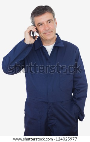 Portrait of mature mechanic using cell phone over white background - stock photo