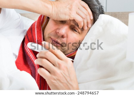 Portrait Of Mature Sick Man Looking At Thermometer - stock photo