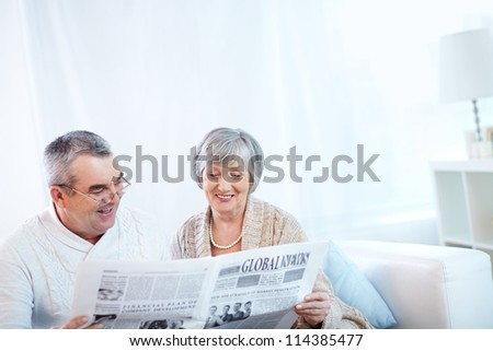 Portrait of mature woman and her husband reading newspaper together - stock photo