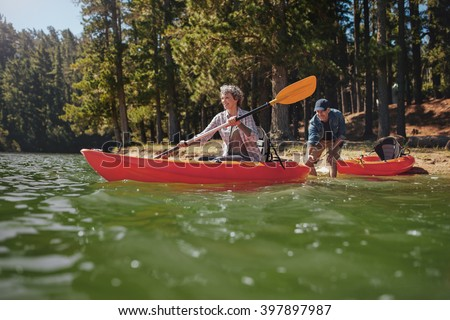Portrait of mature woman canoeing in the lake with man about to catch the kayak from behind. Senior couple having fun kayaking in the lake. - stock photo