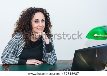 Portrait of mature woman in his studio. With curly hair, blacks or dark, green eyes, on white or clear. - stock photo