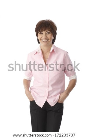 Portrait of mature woman standing hands in pockets, smiling happy. - stock photo