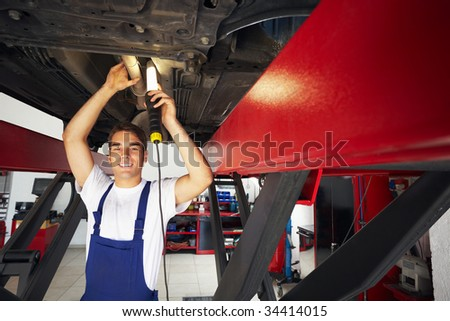 portrait of mechanic standing under car and looking at camera. Copy space - stock photo
