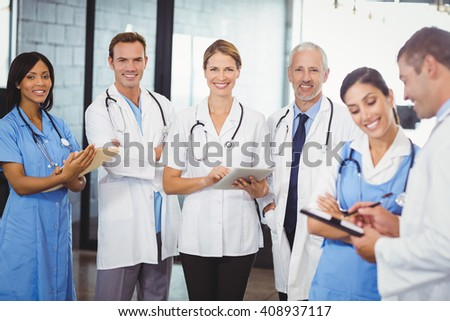 Portrait of medical team standing with file and clipboard in hospital - stock photo