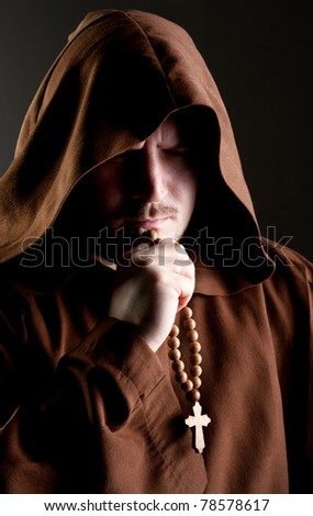 Portrait of medieval monk with cross rosary in shadow - stock photo
