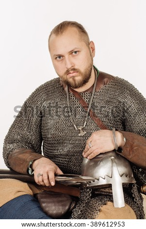 portrait of medieval slavic soldier sitting on fur and looking at camera, with helmet, hauberks, sword and spear. image on white studio background. historical concept. - stock photo