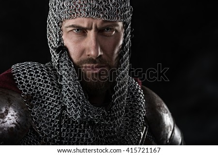 Portrait of Medieval Warrior with chain mail armour and red Cloak. Black Background - stock photo