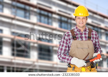 Portrait of mid adult architect holding adjustable wrench against building - stock photo