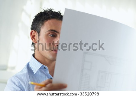 portrait of mid adult architect reading blueprint and smiling - stock photo