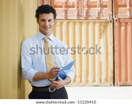 portrait of mid adult businessman leaning on cargo container and looking at camera. Horizontal shape, front view, copy space - stock photo