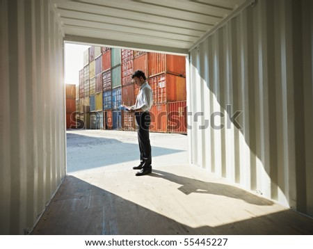 portrait of mid adult businessman standing near cargo container and writing on clipboard. Horizontal shape, side view, copy space - stock photo