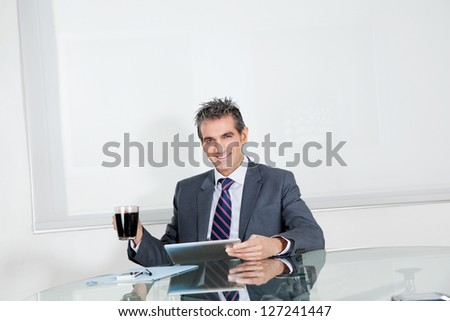 Portrait of mid adult businessman with coffee cup using digital tablet at desk in office - stock photo