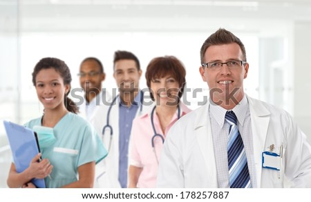 Portrait of mid-adult caucasian male doctor with medical team in background. - stock photo