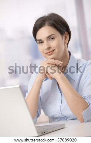 Portrait of mid-adult female office worker smiling at camera sitting with laptop computer.? - stock photo