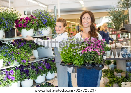 Portrait of mid adult female workers working in flower shop - stock photo