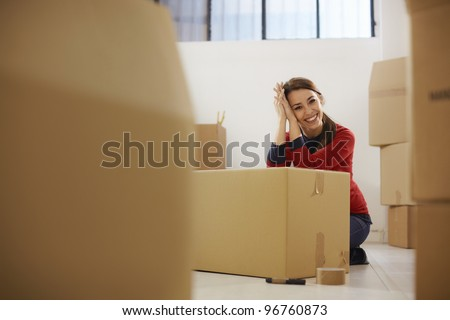 Portrait of mid adult happy woman moving with boxes at new apartment and looking at camera. Copy space - stock photo
