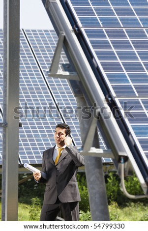 Portrait of mid adult italian male engineer holding blueprints in solar power station and talking on mobile phone. Vertical shape, side view. Copy space - stock photo