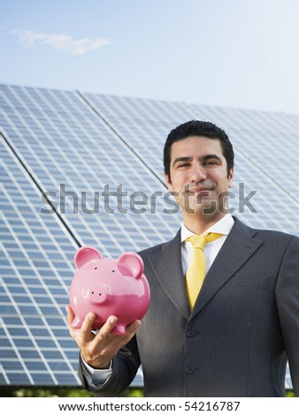 Portrait of mid adult italian male engineer holding piggy bank in solar power station, smiling at camera. Vertical shape, front view. Copy space - stock photo