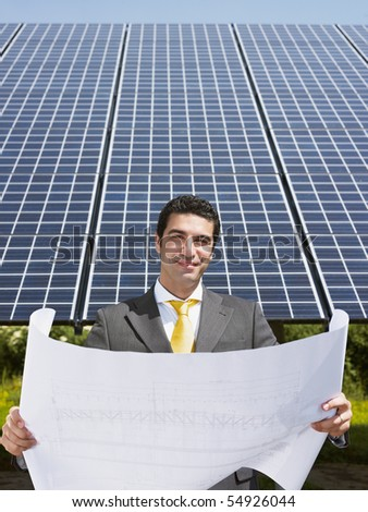 Portrait of mid adult italian male engineer reading blueprints in solar power station and smiling. Vertical shape, front view. Copy space - stock photo