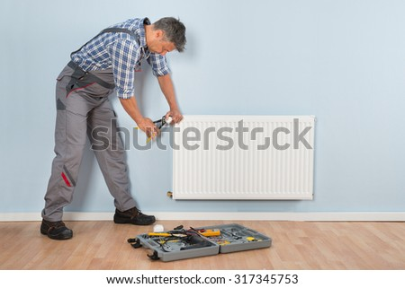 Portrait Of Mid-adult Male Plumber Repairing Radiator With Wrench - stock photo
