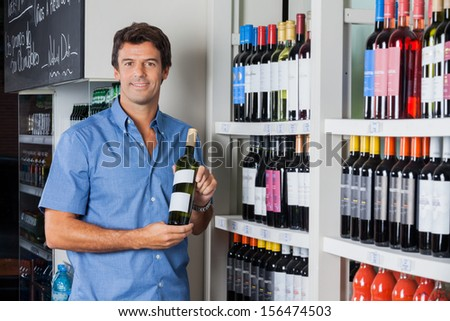 Portrait of mid adult man holding bottle of alcohol at supermarket - stock photo