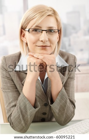 Portrait of mid-adult smart businesswoman smiling at camera, sitting in office.? - stock photo