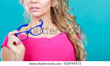 Portrait of mid age attractive woman. Elegant female curly blonde hair posing in vivid color clothing and glasses. Bright fashion. Optics, eyewear. Studio shot on blue background. - stock photo