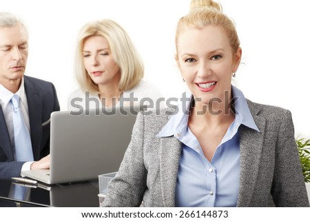 Portrait of middle age business woman standing at business meeting while business people working with laptop at background. - stock photo