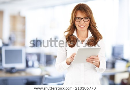 Portrait of middle age businesswoman holding digital tablet and standing at office. - stock photo