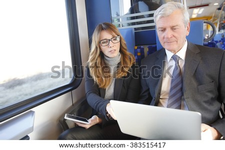 Portrait of middle age businesswoman holding in her hand a digital tablet while senior businessman sitting next to her with his laptop and working online.  - stock photo