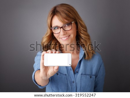 Portrait of middle age businesswoman holding in her hand a mobile phone with blank screen while looking at camera and smiling.  - stock photo