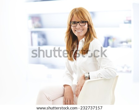 Portrait of middle age casual lawyer sitting at office. Business people.  - stock photo