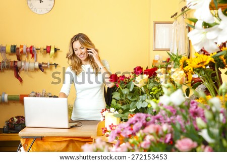 Portrait of middle age florist standing at her flower shop and using her telephone and laptop to take orders for her store.  - stock photo
