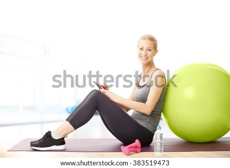 Portrait of middle age sporty woman sitting next to her fitness ball and using her mobile phone while listening music.  - stock photo