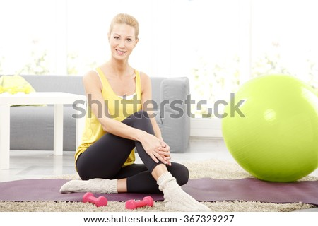 Portrait of middle age woman sitting on a yoga mat at home and relaxing after fitness workout.  - stock photo